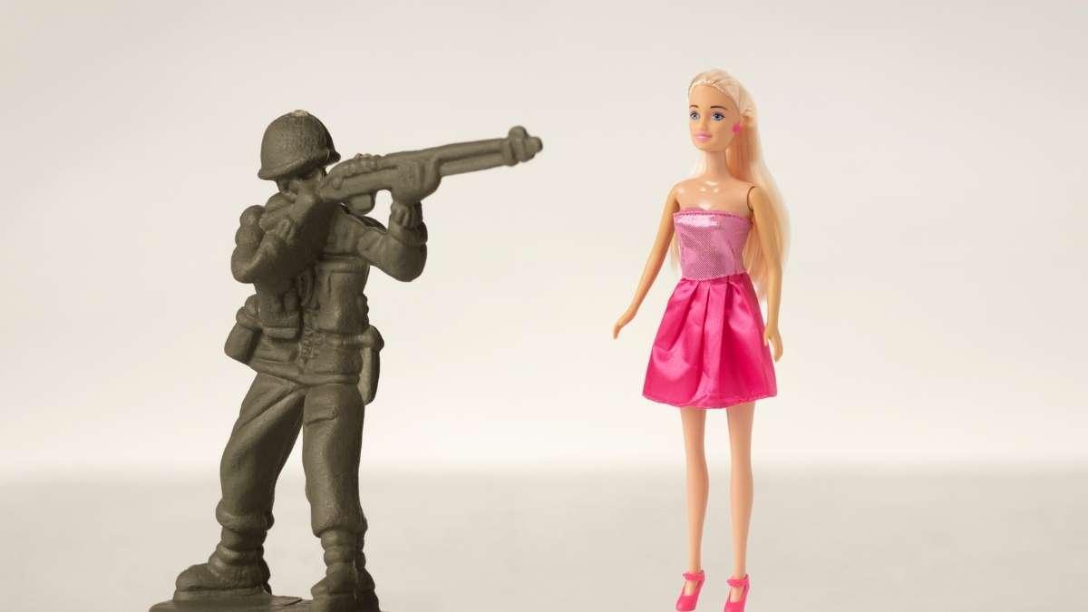 soldado de brinquedo apontando para barbie