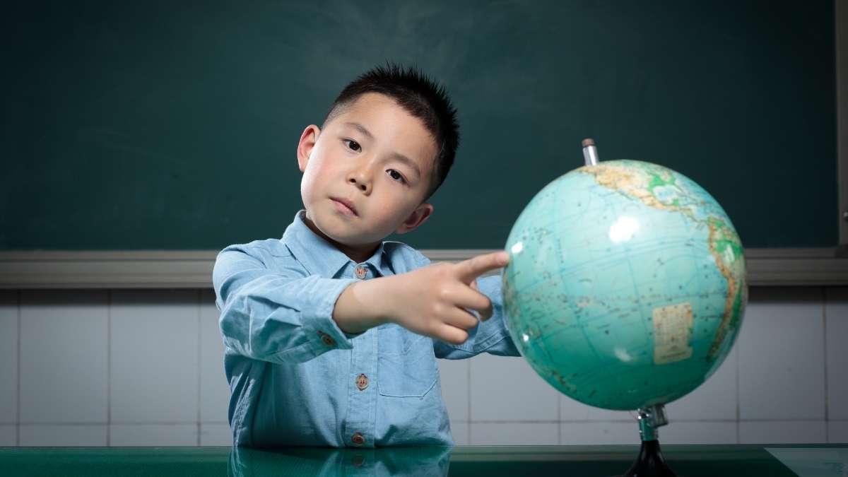 menino apontando para globo terrestre